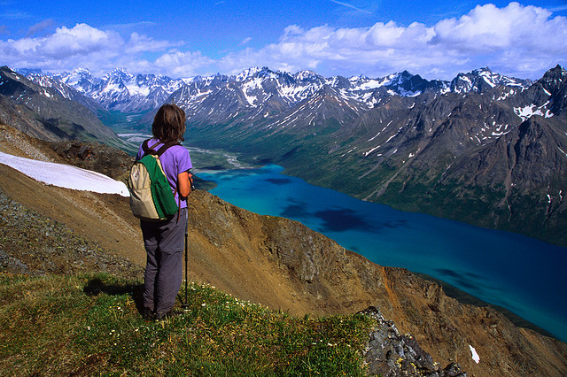 A hiker takes in the view from an overlook above Twin Lakes in Lake Clark National Park and Preserve, Alaska