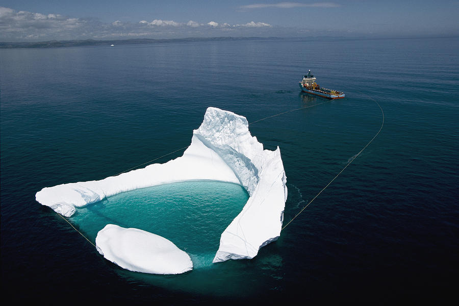 Ship towing an iceberg off the shore of Newfoundland / Canada ,